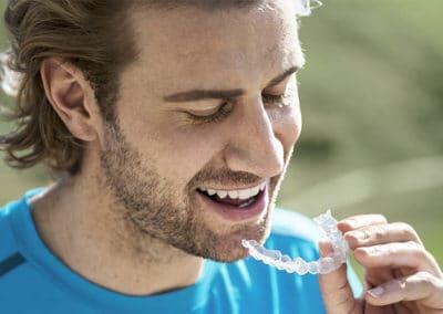 Hombre joven usa ortodoncia removible invisible Invisalign
