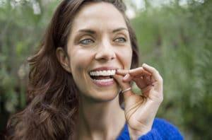 20 preguntas de ortodoncia - Mujer joven lleva ortodoncia invible Invisalign