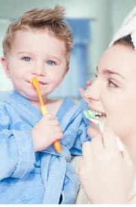 Madre enseña a niño como cepillar los dientes, evitando así tener caries en un futuro