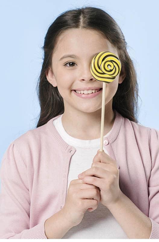 Niña tiene cuidado de no comer demasiados dulces para no tener caries