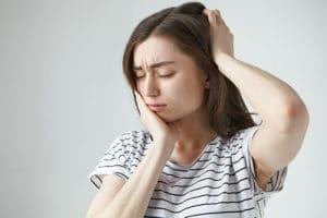 Chica sufre dolor en dientes y cabeza provocados por el bruxismo
